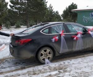 Kar nedeniyle yolda kalan gelin arabasını damat itekledi