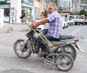 Koltuk değnekli sürücü kucağındaki çocukla motosiklet kullandı